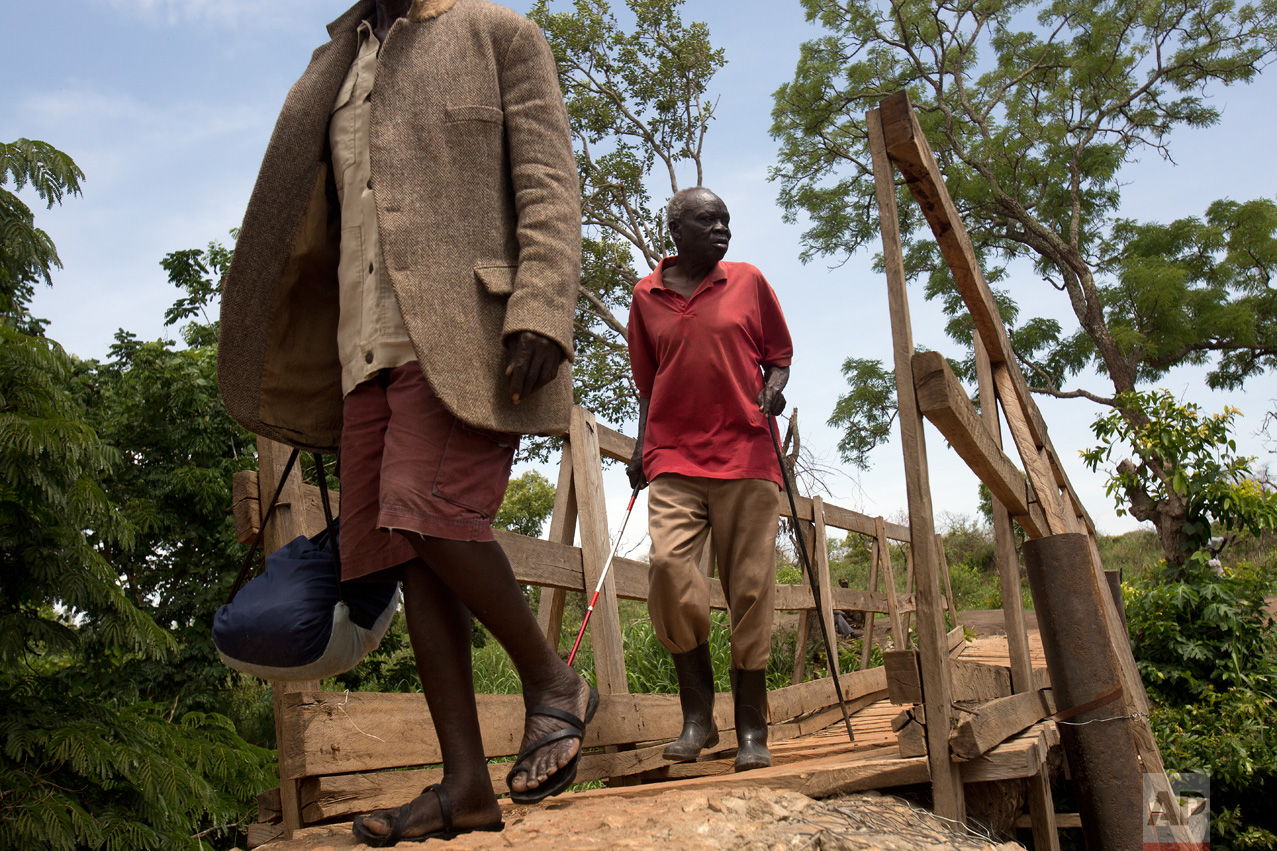 In this Wednesday March 29, 2017 photo, Ringo Gwiya, 80, a blind South Sudanese refugee, crosses the bridge over the Kaya River linking South Sudan to Uganda near Busia. (AP Photo/Jerome Delay)
