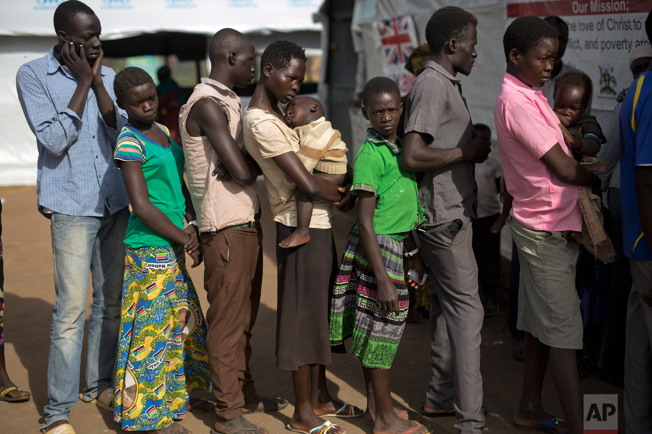 In this Thursday March 30, 2017 photo, South Sudanese refugee Mary Kide and her son, Desem, stand in line with others, including Samson Tabani, left, to get a medical check up at the Kuluba transit camp. (AP Photo/Jerome Delay)