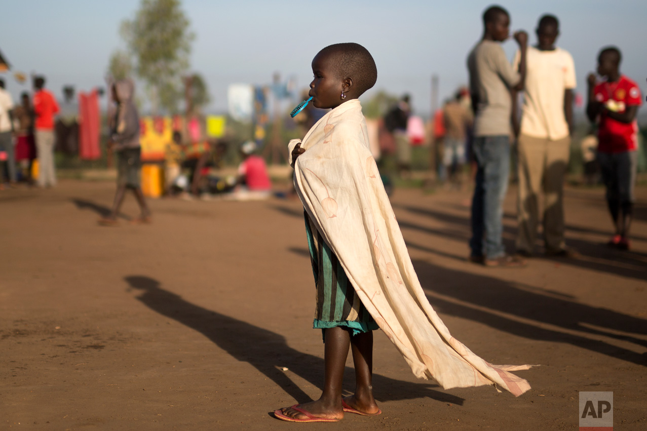 In this Friday March 31, 2017 photo, Vickie, 4, holds a hair brush in her mouth she walks in the Kuluba, Uganda, transit camp. (AP Photo/Jerome Delay)