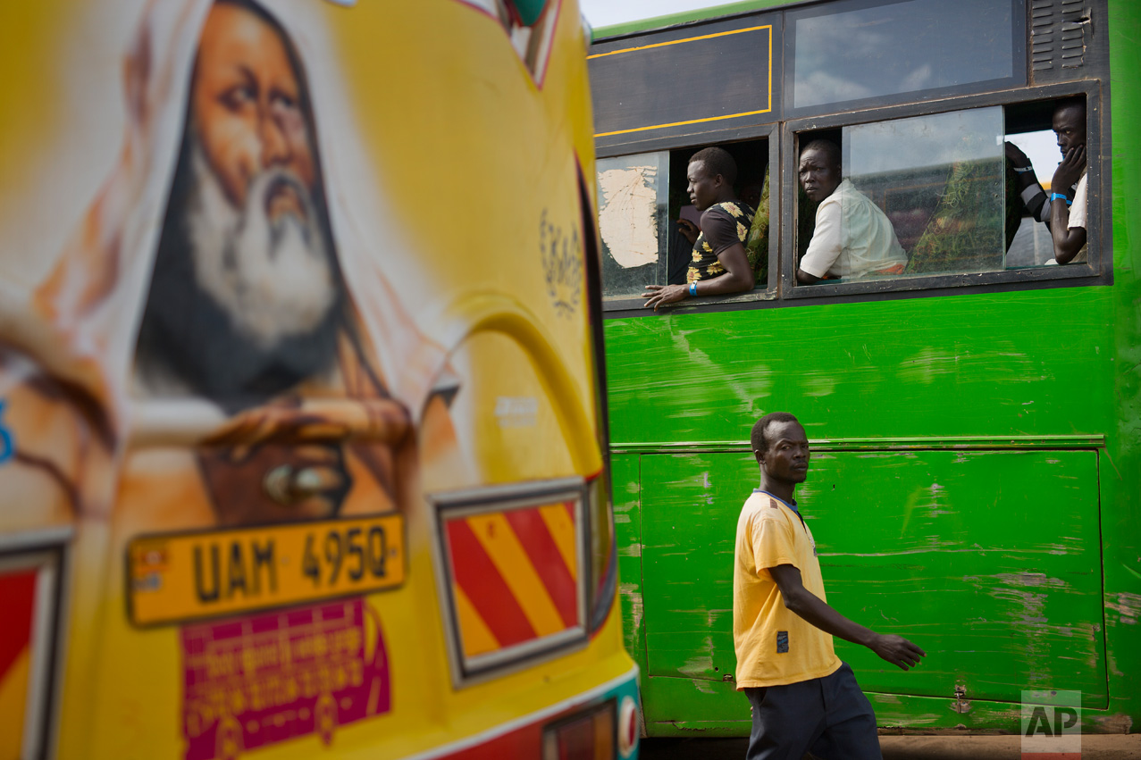 In this Friday March 31, 2017 photo, South Sudanese refugees board buses at the Kuluba transit camp in Uganda. Over 1000 refugees transit daily through Kuluba and are then transported to Imvepi for permanent settlement. (AP Photo/Jerome Delay)