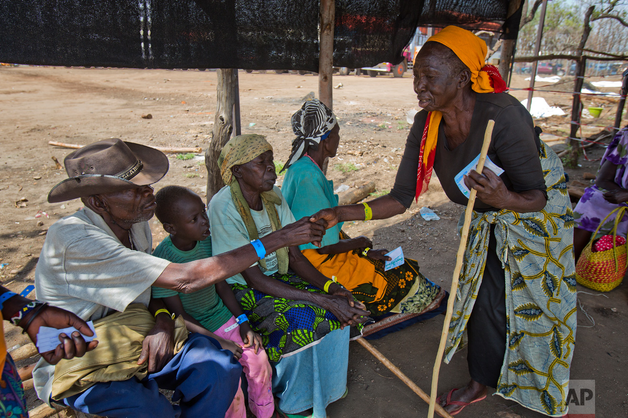 In this Friday, March 31, 2017 photo, Alfred Wani greets an elderly South Sudanese woman as they wait for medical help at the Imvepi refugee settlement in northern Uganda. (AP Photo/Jerome Delay)
