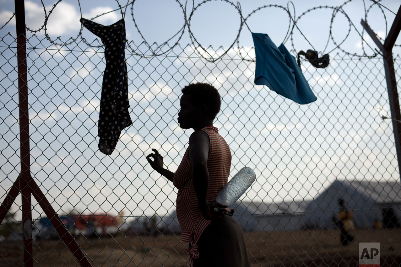 In this Saturday, April 1, 2017 photo, Ide Djen, 29, a South Sudanese refugee from Kenienba, holds an empty bottle of water as she waits by water pumps in the Imvepi refugee settlement in northern Uganda. (AP Photo/Jerome Delay)