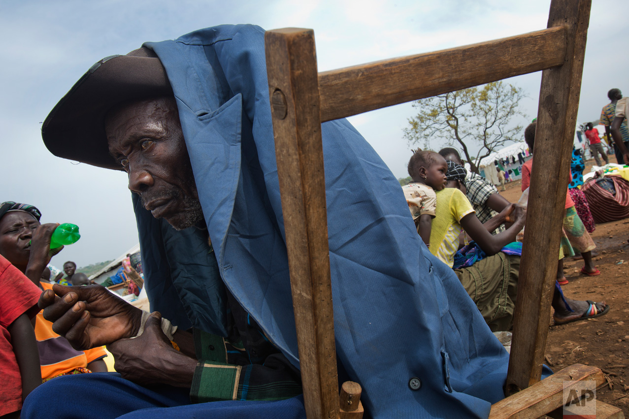 In this Tuesday, April 4, 2017 photo in the Imvepi camp, Alfred Wani and his family wait to load their belongings in trucks to be taken to the plots of land they were allocated by the Ugandan government for their resettlement. (AP Photo/Jerome Delay)