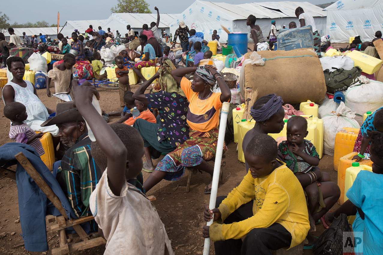 In this Tuesday, April 4, 2017 photo in the Imvepi camp, Alfred Wani and his family wait to load up their belongings in trucks to be taken to the plots of land they were allocated by the Ugandan government for their resettlement. (AP Photo/Jerome Delay)