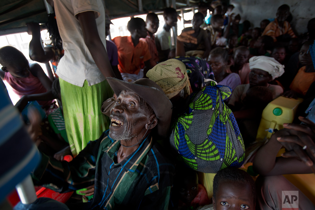 In this Tuesday, April 4, 2017 photo in the Imvepi camp, Alfred Wani and his family travel in trucks to the plots of land they were allocated by the Ugandan government for their resettlement. (AP Photo/Jerome Delay)