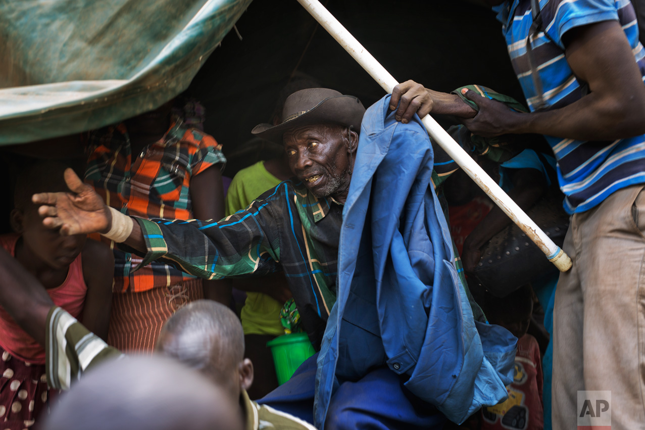In this Tuesday, April 4, 2017 photo in the Imvepi camp, Alfred Wani disembarks from a truck that took him and family to the plots of land they were allocated by the Ugandan government for their resettlement. (AP Photo/Jerome Delay)