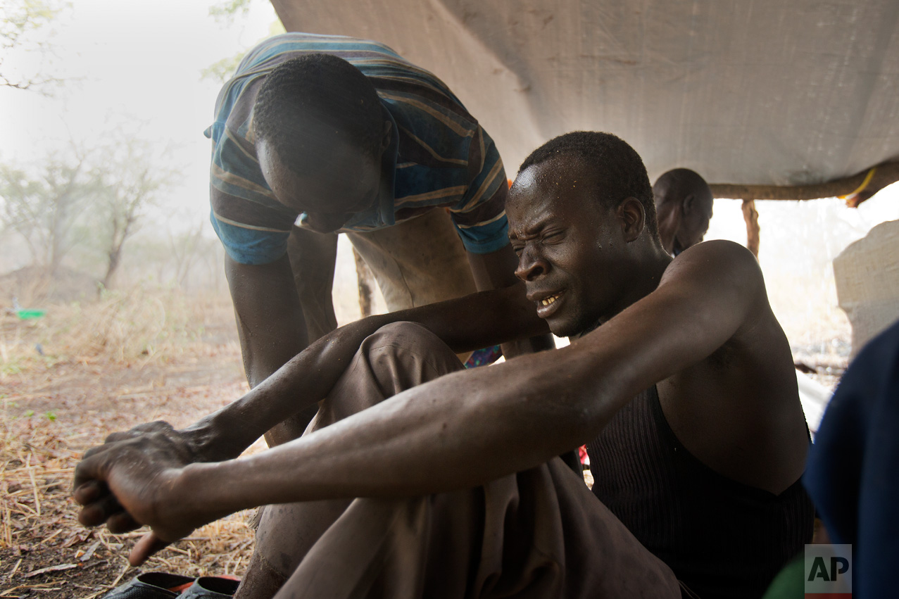 In this Wednesday, April 5, 2017 photo in the Imvepi camp, Samson Wani comforts his uncle, Michael Lowe, during a rain storm on the plot of land he and family were allocated by the Ugandan government for their resettlement. (AP Photo/Jerome Delay)