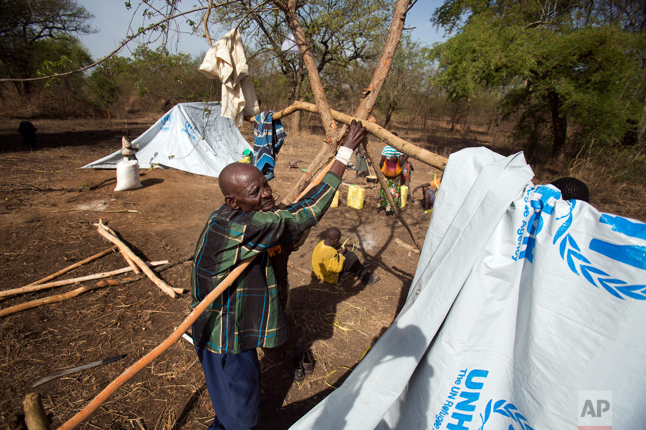 """In this Thursday, April 6, 2017 photo in the Imvepi camp, Alfred Wani builds a temporary shelter that will be called home on the plot of land he and family were allocated by the Ugandan government for their resettlement. Wani, a farmer, shares a few regrets: """"If I was young again, I would raise more cattle, and build a good house in concrete, and also pay for my kids' school. I didn't go to school and neither did my children."""" (AP Photo/Jerome Delay)"""