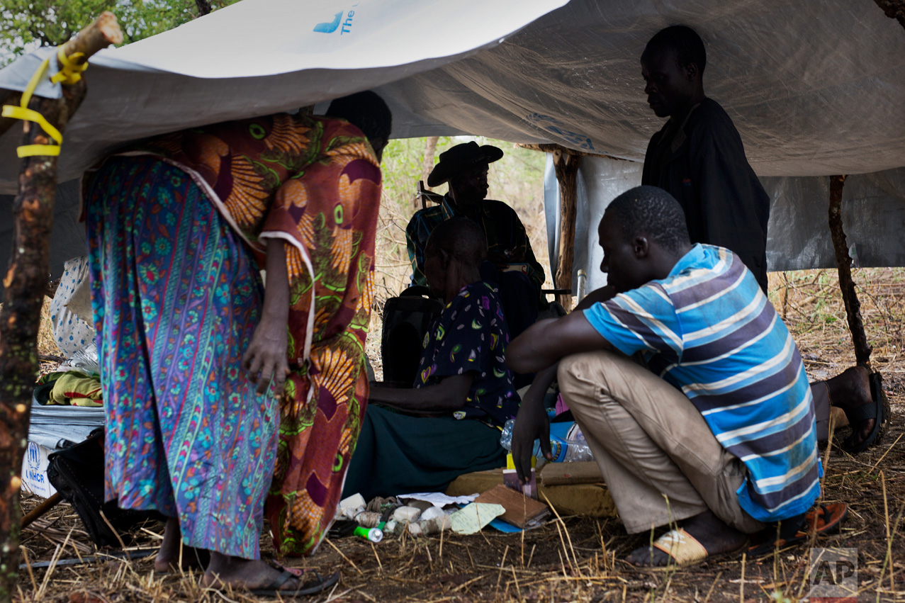 In this Thursday, April 6, 2017 photo in the Imvepi camp, Alfred Wani sits with relatives in their just-built temporary shelter that will be called home on the plot of land he and his family were allocated by the Ugandan government for their resettlement. (AP Photo/Jerome Delay)