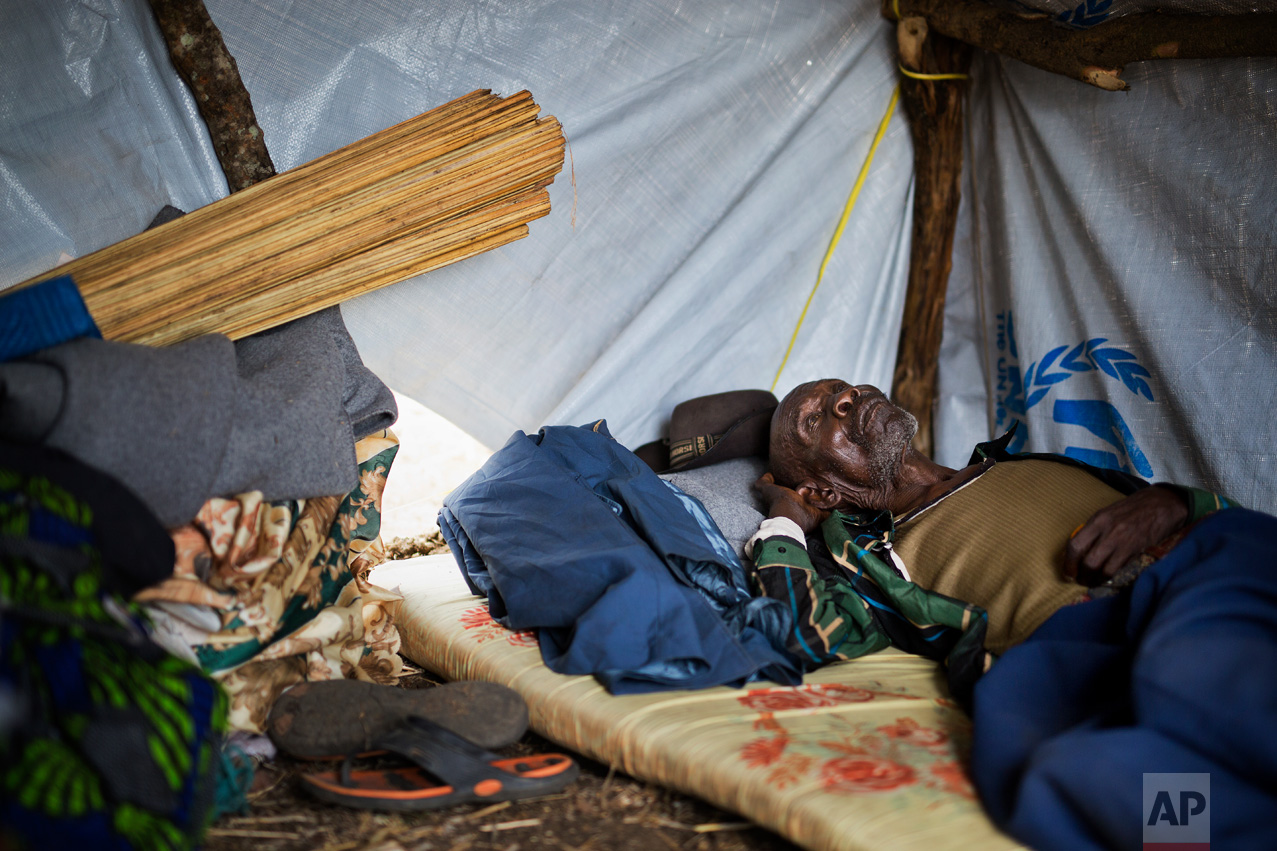 """In this Thursday, April 6, 2017 photo in the Imvepi camp, Alfred Wani rests in the just built temporary shelter that will be called home on the plot of land he and family were allocated by the Ugandan government for their resettlement. Wani, a farmer, shares a few regrets: """"If I was young again, I would raise more cattle, and build a good house in concrete, and also pay for my kids' school. I didn't go to school and neither did my children."""" (AP Photo/Jerome Delay)"""