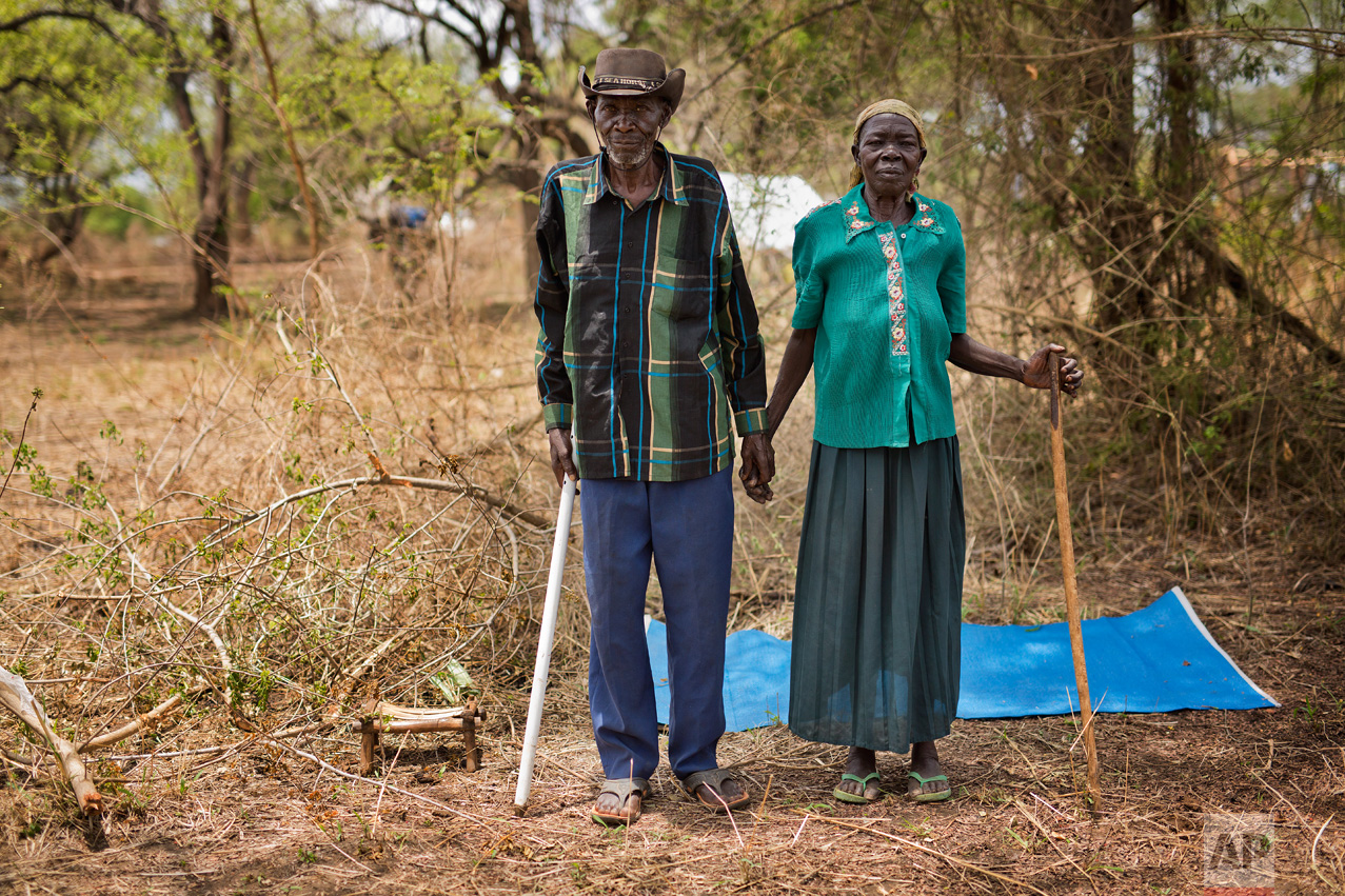 """In this Friday, April 7, 2017 photo in the Imvepi camp, Alfred Wani and his wife Kassa pose for a formal photo on the plot of land they were allocated by the Ugandan government for their resettlement. The couple does not hold out hope of returning home to South Sudan. """"I saw the killing, I saw burning houses, I saw the dead with their throats slashed,"""" Alfred says. """"I cannot go back and see it again."""" (AP Photo/Jerome Delay)"""