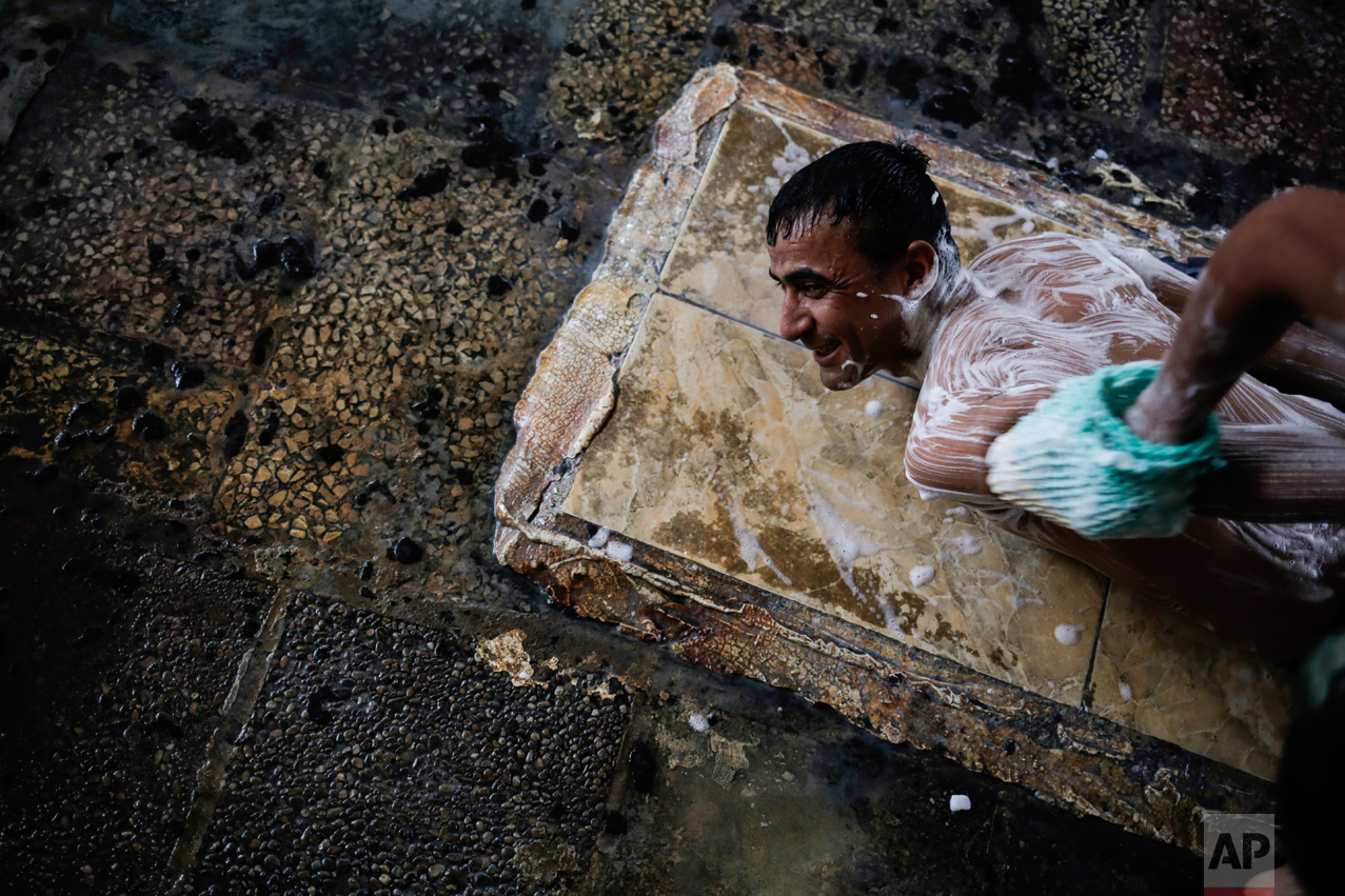 A customer of the Hamal Alil sulphur spa gets a scrub and massage south of Mosul, Iraq, on Thursday, April 27, 2017. Many Iraqi soldiers visit the spa in between fighting against the Islamic State group for relaxation. (AP Photo/Bram Janssen)
