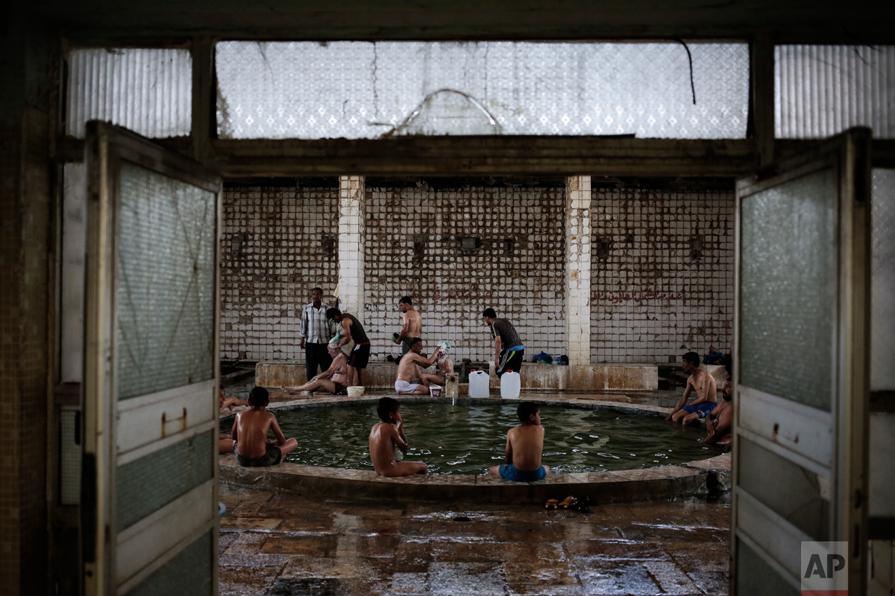 Customers enjoy the Hamam Alil sulphur spa, situated in an historic building half an hour south of Mosul, Thursday, April 27, 2017. Before the Islamic State took over the town of Hamam Alil in 2014, people from all over Iraq visited the historic spa. (AP Photo/Bram Janssen)