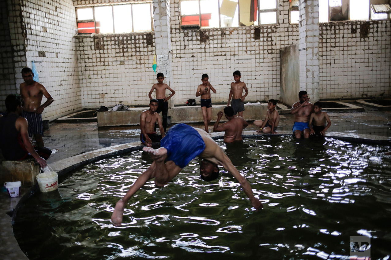 A customer jumps into the pool filled with water from a sulphur well in Hamam Alli, south of Mosul, Iraq, Thursday, April 27, 2017. Before the Islamic State took over the town of Hamam Alil in 2014, people from all over Iraq visited the historic spa south of Mosul. (AP Photo/Bram Janssen) (AP Photo/Bram Janssen)