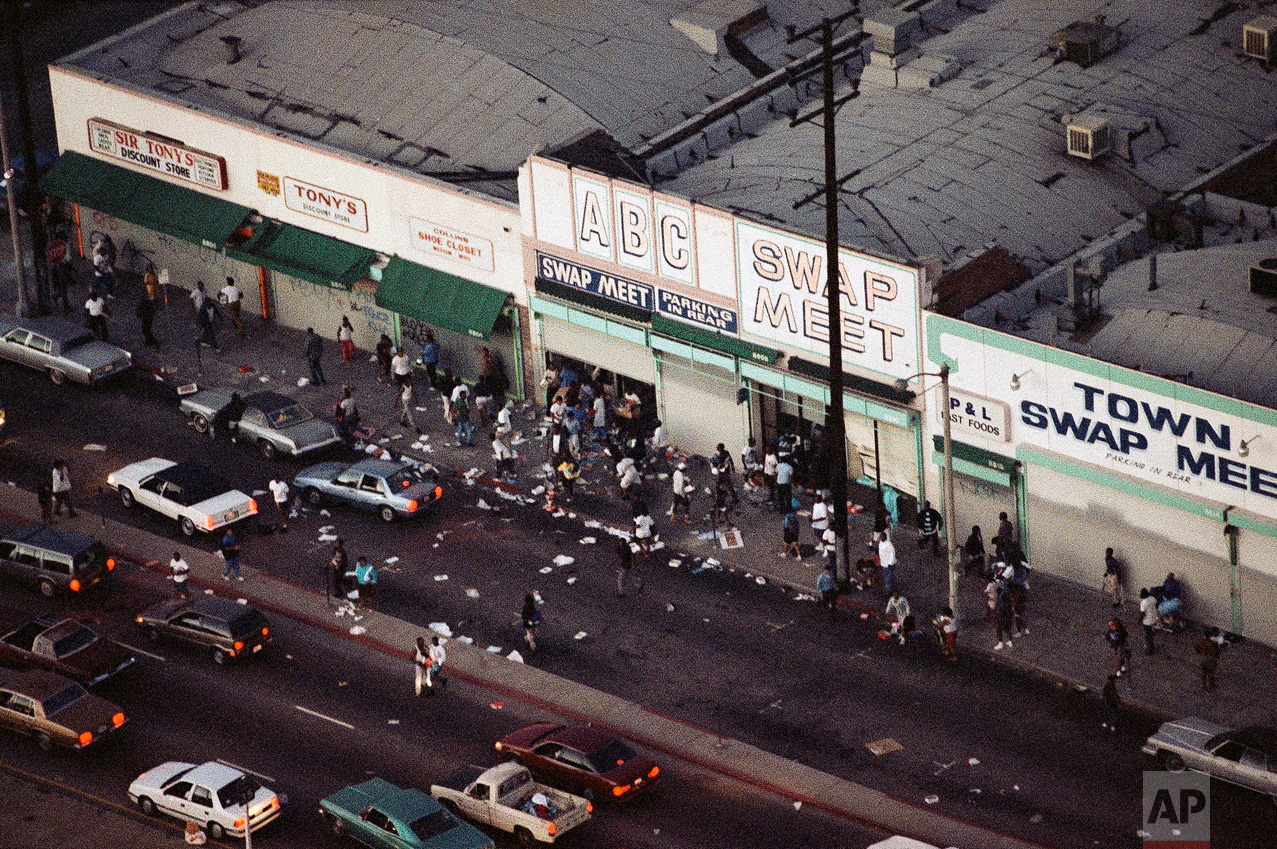 In this Wednesday, April 29, 1992 photo, people enter and leave a swap meet in South Central Los Angeles. Violence broke out in the area after four Los Angeles police officers were acquitted on all but one charge for the videotaped beating of motorist Rodney King. (AP Photo/Reed Saxon)