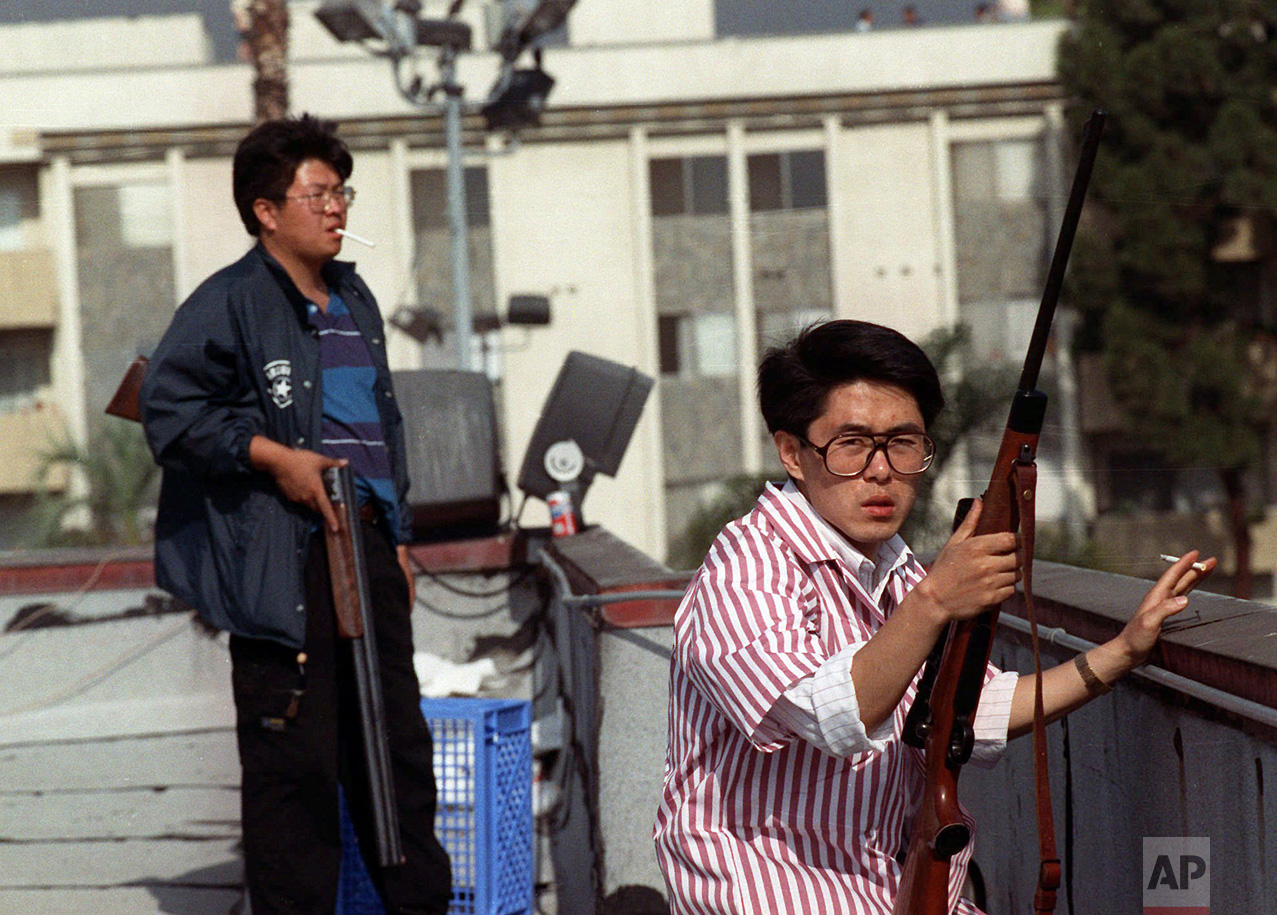 In this April 30, 1992 photo, two Korean men stand on the roof of a grocery store with rifles to prevent looters from entering in Los Angeles. On April 29, 1992, four white police officers were declared innocent in the beating of black motorist Rodney King, and Los Angeles erupted in the deadliest riots of the century. Three days later, 55 people were dead and more than 2,000 injured. Fires and looting had destroyed $1 billion worth of property. (AP Photo/John Gaps III)