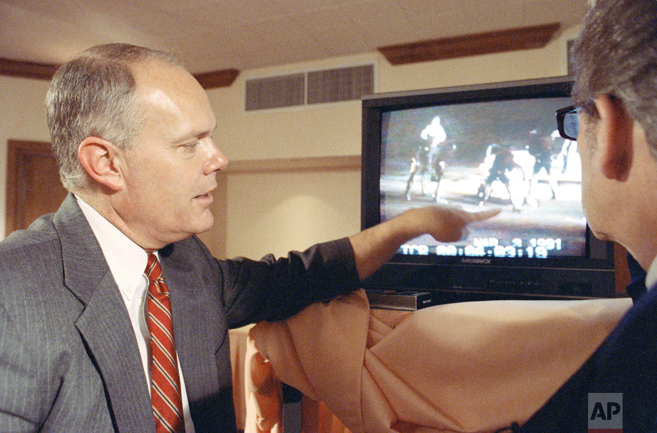 """In this Saturday, April 18, 1993 photo, Los Angeles police officer Stacey Koon describes what is happening on the Rodney King beating video to host Steve Dunleavy at a hotel in Valencia, Calif., during the taping of the syndicated television show """"A Current Affair."""" Koon was interviewed shortly after he was found guilty in the Rodney King civil rights trial. (AP Photo/Douglas C. Pizac)"""