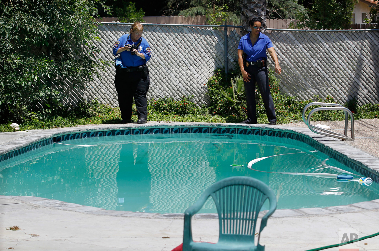 In this Sunday, June 17, 2012 photo, police detective Carla McCullough, right, and a photographer conduct an investigation at Rodney King's home in Rialto, Calif. King, the black motorist whose 1991 videotaped beating by Los Angeles police officers was the touchstone for one of the most destructive race riots in U.S. history, died Sunday. He was 47. King's fiancee called police to report that she found him at the bottom of the swimming pool at their home in Rialto, Calif., police Lt. Dean Hardin said. (AP Photo/Jae C. Hong)