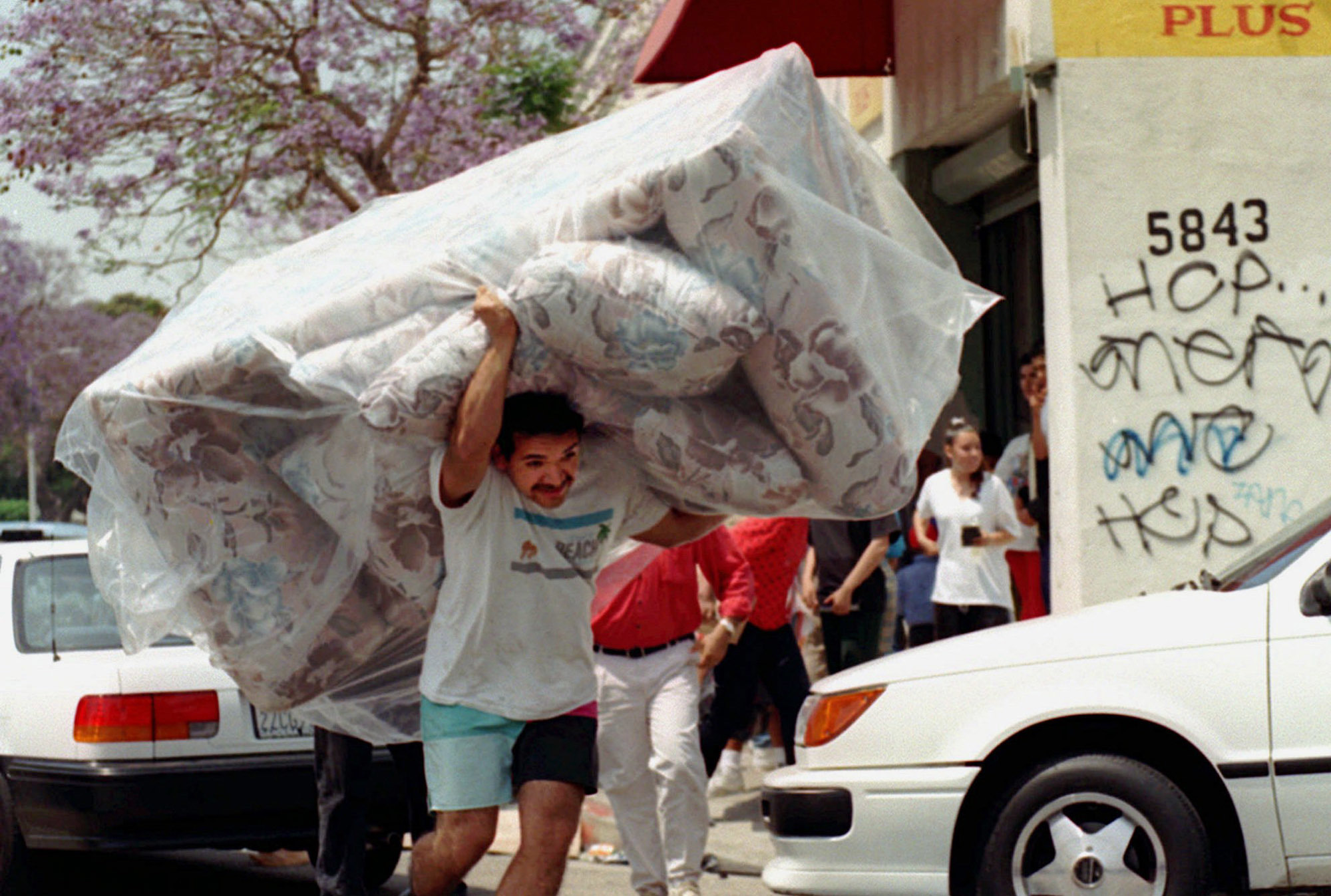 In this April 30, 1992 photo, a man carries a couch from a store in South Central Los Angeles as looting and rioting continued throughout the area. (AP Photo/Nick Ut)