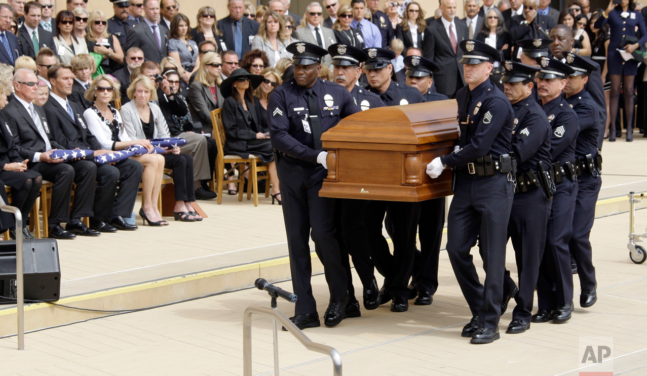 A police honor guard carries the casket following a public memorial service for retired Los Angeles Police Chief Daryl F. Gates, following a private funeral service, at the Cathedral of Our Lady of the Angels in Los Angeles Tuesday, April 27, 2010. Seated from left are Gates' brother Steve Gates, son Scott Gates, daughters Kathy Gates Perricone and Debbie Ledesma, and Gates' longtime companion Gina Velardi, in hat. (AP Photo/Reed Saxon)