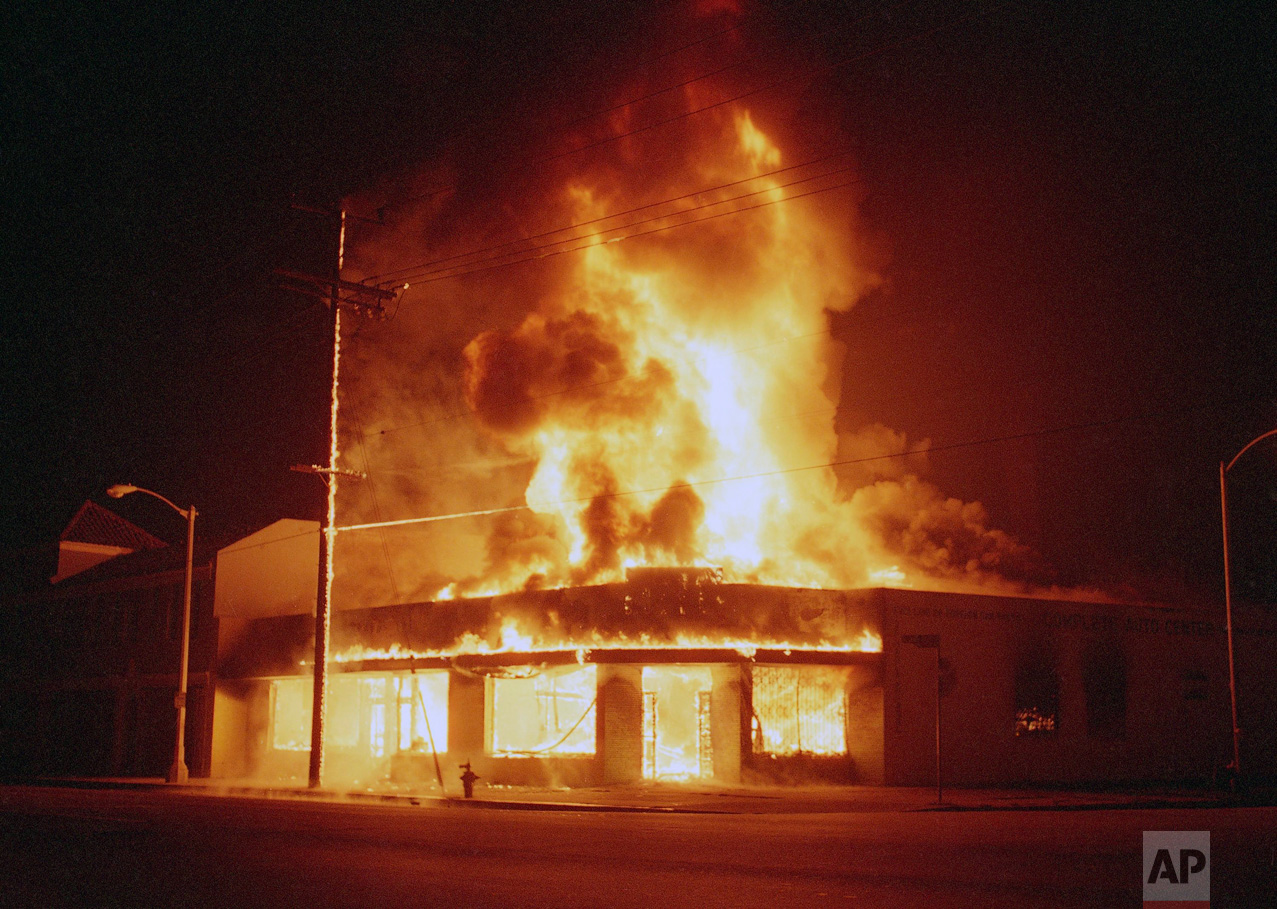 With flames leaping over 50 feet into the night sky, an auto parts store burns out of control in Los Angeles, Thursday, April 30, 1992. Numerous fires were set and stores were looted after the Rodney King beating trial verdict. (AP Photo/Douglas C. Pizac)