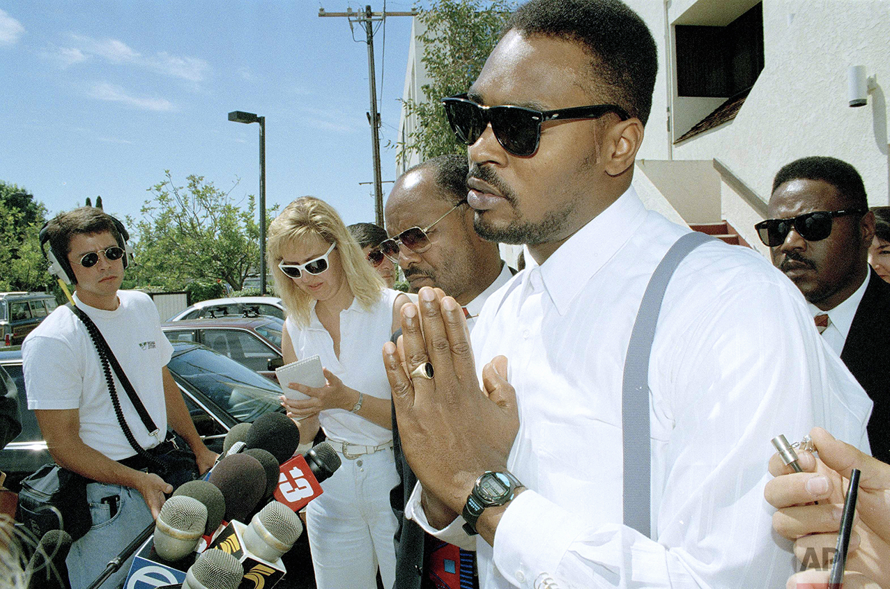 Rodney King makes a point at a news conference in Santa Ana, Calif., June 2, 1994. Jurors who earlier ordered the city of Los Angeles to pay King $3.8 million for his beating declined to order punitive damages against any of the police officers involved in the March 1991 video taped beating. King's attorney Milton Grimes looks on second from right. (AP Photo/Chris Martinez)