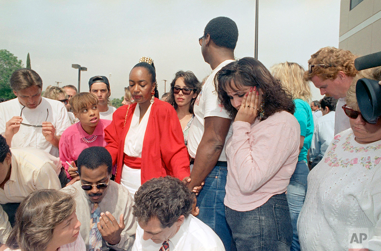 Patricia Moore, second from left, J.D. Rosborough, second from right and Sandy Martinez, right, react with anger and tears at the acquittal of four Los Angeles police officers in the Rodney King assault case in Simi Valley, California on Wednesday, April 30, 1992. All officers were found not guilty with the exception of one charge against Laurence Powell in which the jury was undecided. (AP Photo/Nick Ut)