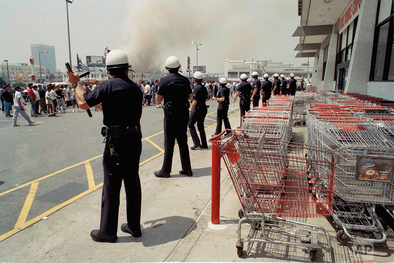 Los Angeles police form a line to prevent a crowd from going into a building, April 30, 1992, in a day of fires and looting. It was a long day as officers moved from trouble spot to trouble spot. (AP Photo/Nick Ut)