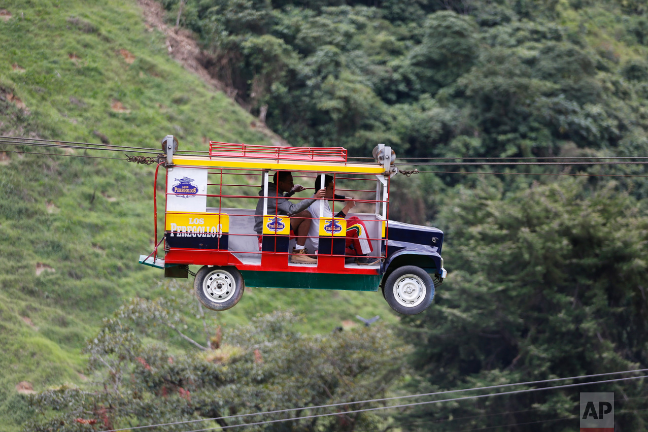 """Tourists ride a cable car in the form a of a Chiva, a bus used to serve rural routes, in Pitalito, Colombia, Tuesday, April 5, 2017. The ride called """"La Chiva Voladora"""" costs about $0.70 and you zip along from about 800 meters from one side of a hill to another. (AP Photo/Fernando Vergara)"""