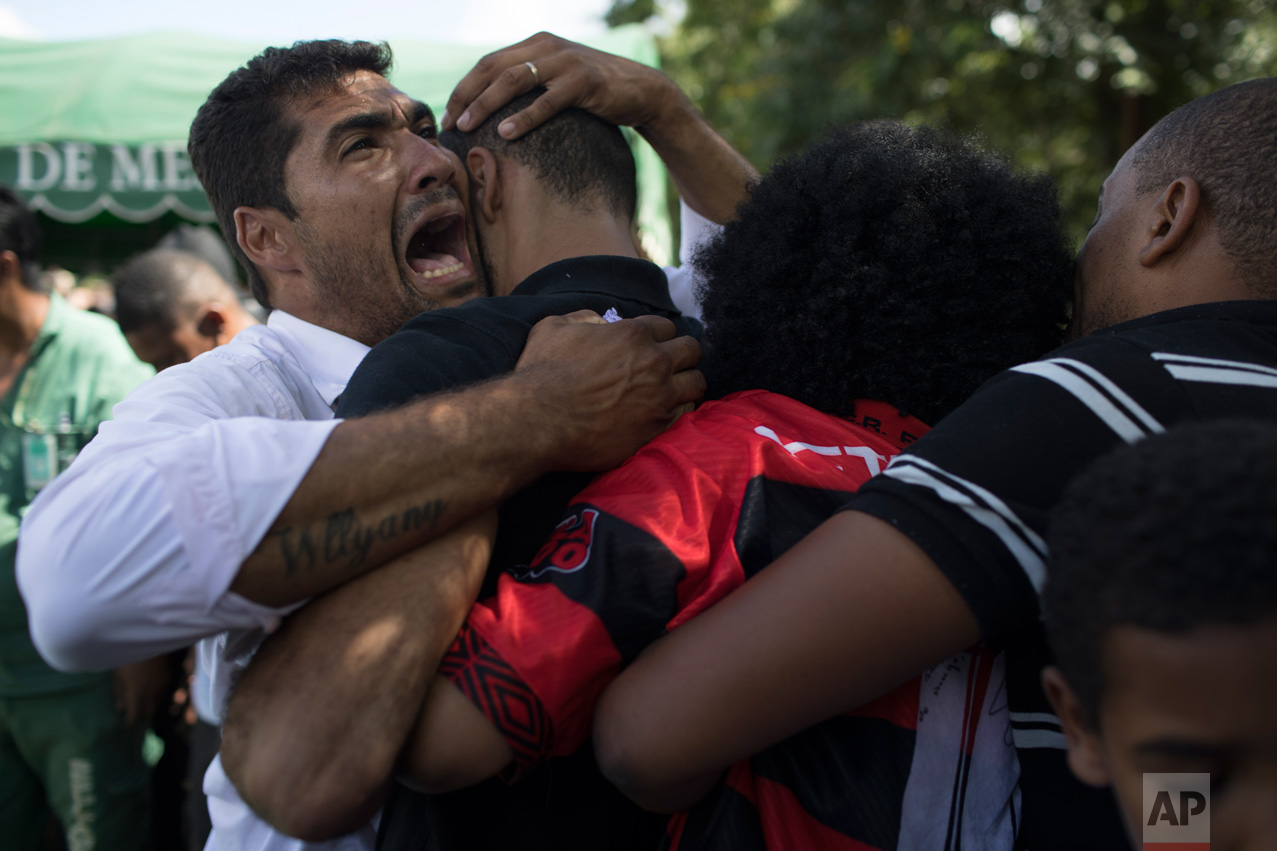 Relatives cry during the burial of 13-year-old Maria Eduarda Alves da Conceicao, who was killed by a stray bullet during a shootout between police and alleged drug traffickers in Rio de Janeiro, Brazil, Saturday, March 1, 2017. A video showing the Thursday confrontation between police and suspect drug traffickers was shared widely on social media and led to protests. In the video, two officers are seen carrying automatic rifles. They both shoot suspects on the ground. One of the men appears to be moving when he is shot. Rio de Janeiro police spokesman Ivan Blaz told reporters on Friday that the two officers have been charged with murder. (AP Photo/Leo Correa)