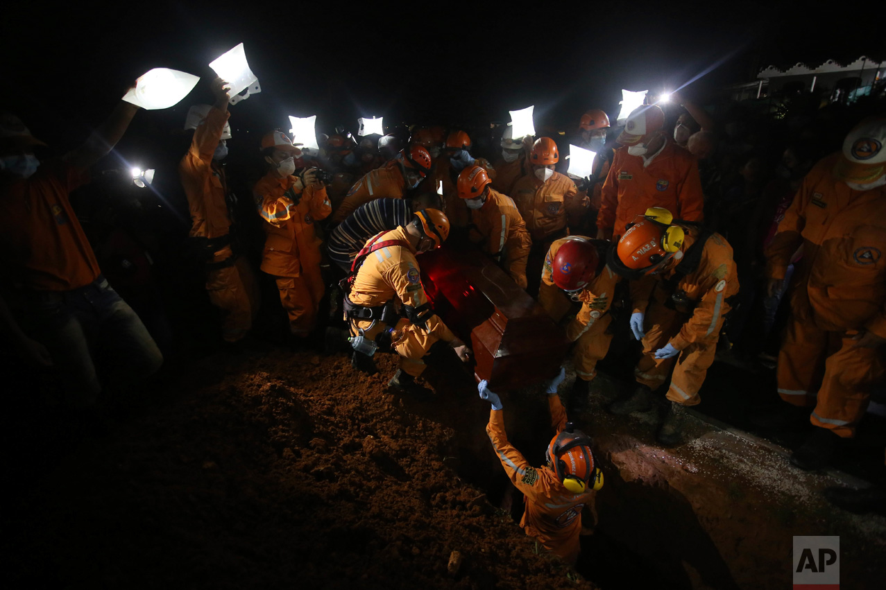 Rescue workers bury their comrade Jesus Diago, who was killed while rescuing his family, in Mocoa, Colombia, Tuesday, April 4, 2017. Diago was killed when surging rivers sent an avalanche of floodwaters, mud and debris sweeping him away as he attempted to carry a cousin to safety.  He had already managed to save the rest of his family and the young cousin was the last one to be rescued when they were both swept away and killed. (AP Photo/Ivan Valencia)