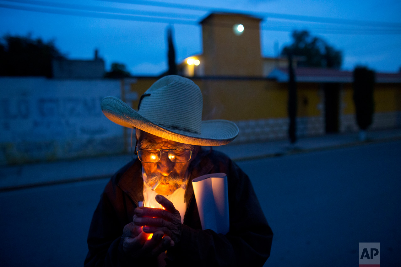 """In this March 31, 2017 photo, farmer Manuel Ortega, 89, lights a cigarette following a strategy meeting by farmers in Tepatepec, Hidalgo state, Mexico. Ortega, who still works in the fields and gets around town by bicycle, said he was raised on the leafy greens, beans and zucchini grown here. """"It never gave me the runs,"""" he added with a laugh. (AP Photo/Rebecca Blackwell)"""