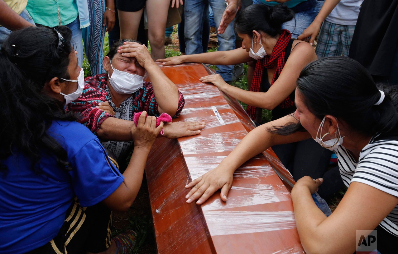 Women cry over the coffin of a relative, a victim of a deadly avalanche due to heavy rains, during a mass burial in Mocoa, Colombia, Monday, April 3, 2017. The grim search continues for the missing in southern Colombia after surging rivers sent an avalanche of floodwaters, mud and debris through the small city, killing more than 260 people and leaving many more injured and homeless. (AP Photo/Fernando Vergara)