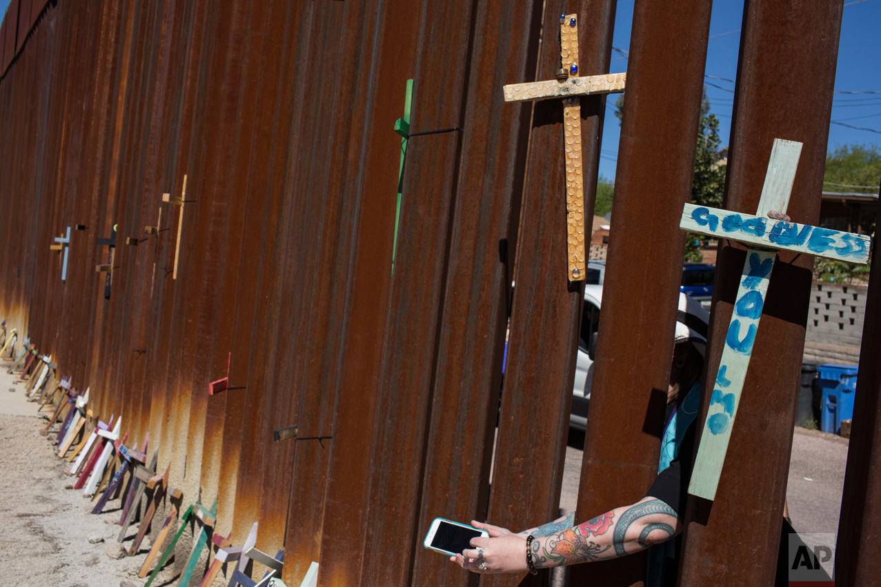 """In this Sunday, April 2, 2017 photo, Rachel Baker, a Unitarian minister from Las Vegas, Nev., puts her arms through the slats of the U.S.-Mexico border fence, to make a selfie as she takes part in a solidarity march in Nogales, Ariz. Baker argues we should be tearing down the existing barrier instead of talking about building a bigger one. """"I think it's a terrible idea,"""" she says. """"I'm not interested in separating families."""" (AP Photo/Rodrigo Abd)"""