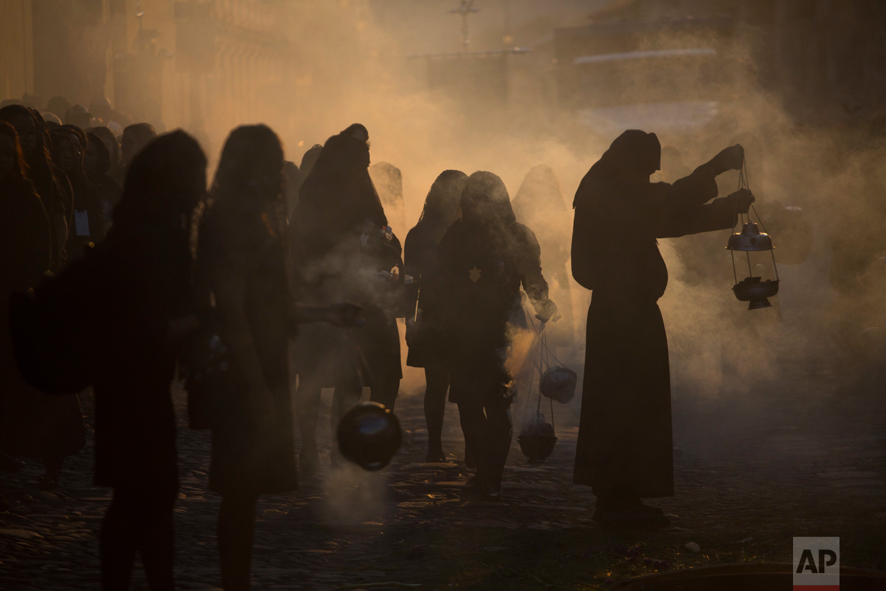 La Escuela de Cristo Catholic Church penitents burn incense during an afternoon procession through the streets of Antigua, Guatemala, Friday, April 14, 2017. Hundreds of processions take place throughout Guatemala during the Holy Week. (AP Photo/Moises Castillo)