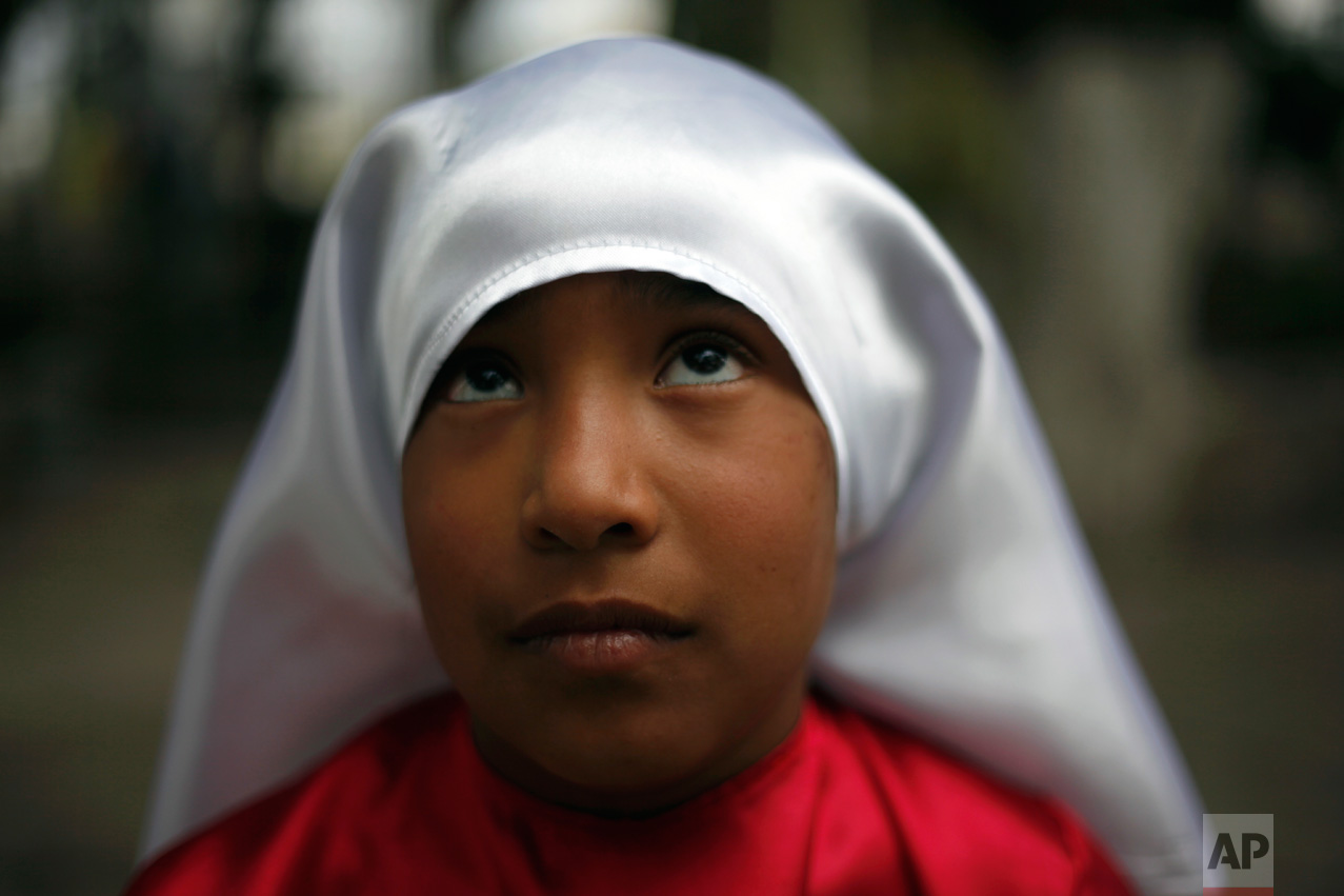 A girl dressed to participate in a reenactment of the Via Crucis, or Way of the Cross, waits for a practice in the village of San Mateo, some 50 km north of Mexico City, Mexico, Thursday April 13, 2017. Holy Week commemorates the last week of the earthly life of Jesus Christ culminating in his crucifixion on Good Friday and his resurrection on Easter Sunday. (AP Photo/Marco Ugarte)