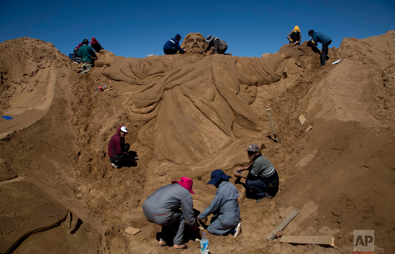 Artists works on a sand sculpture depicting Jesus Christ, during Holy Week celebrations in Arenal de Cochiraya, on the outskirts of Oruro, Bolivia, Friday, April 14, 2017. Two hundred artists gathered for the annual Good Friday event in the highland region, building sand sculptures based on the parables of Jesus. (AP Photo/Juan Karita)