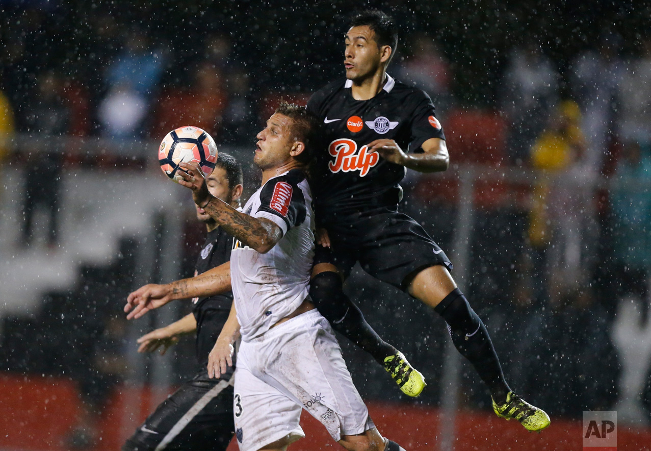 Rafael Moura, left, of Brazil's Atletico Mineiro fights for the ball with Luis Cardozo of Paraguay's Libertad during a Copa Libertadores soccer match in Asuncion, Paraguay, Wednesday, April 19, 2017.(AP Photo/Jorge Saenz)