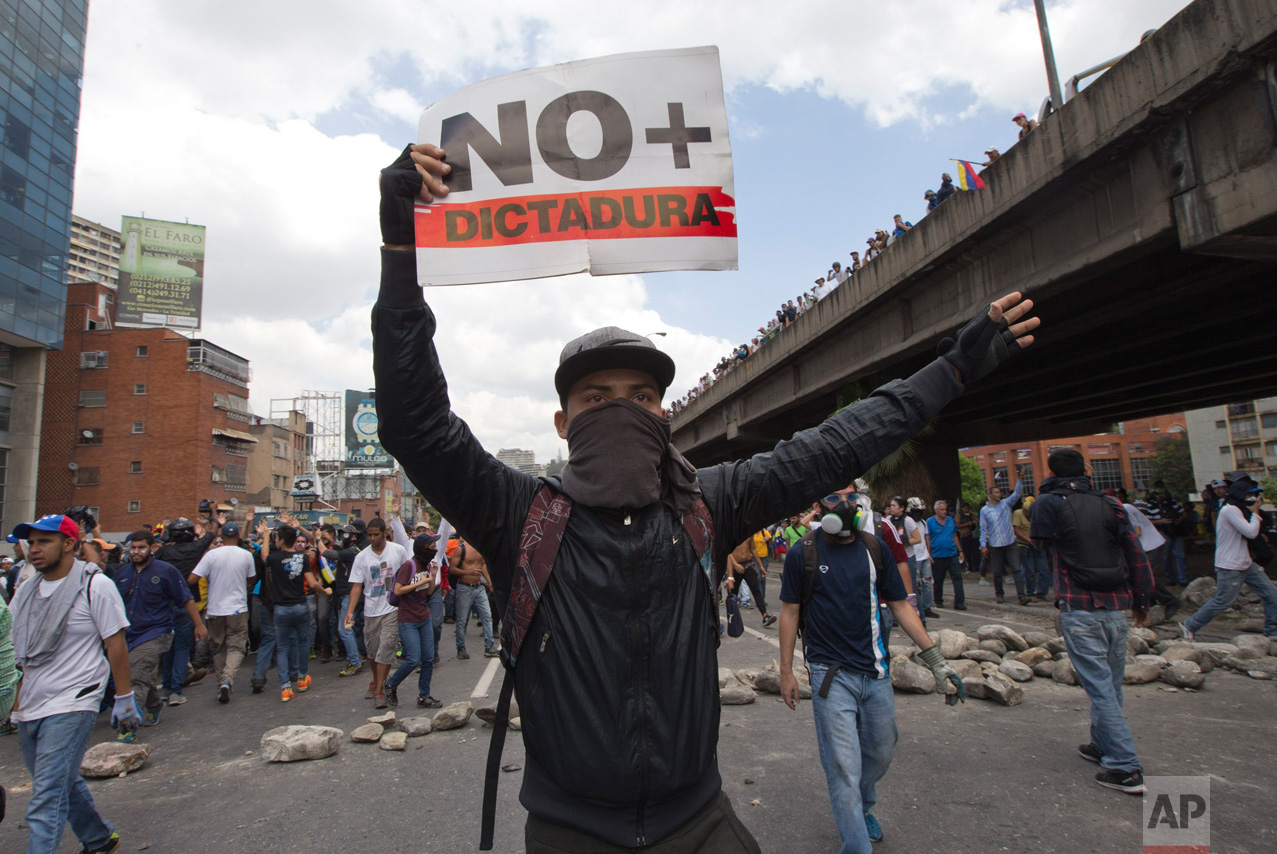 """A demonstrator holds up a sign that reads in Spanish read """"No more dictatorship"""" during a protest in Caracas, Venezuela, Thursday, April 6, 2017. The South American country has seen near-daily protests since the Supreme Court issued a ruling nullifying congress last week. The court pulled that decision back after it came under heavy criticism, but opposition leaders said the attempt to invalidate a branch of power revealed the administration's true dictatorial nature. (AP Photo/Ariana Cubillos)"""