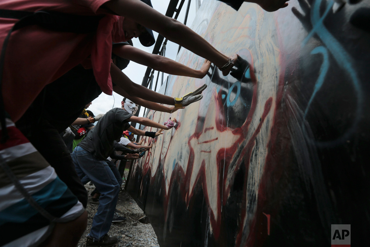 """Ant-Government protesters tear down an iron gate in Caracas, Venezuela, Wednesday, April 19, 2017. Tens of thousands of opponents of President Nicolas Maduro flooded the streets of Caracas in what's been dubbed the """"mother of all marches"""" against the embattled president. (AP Photo/Fernando Llano)"""