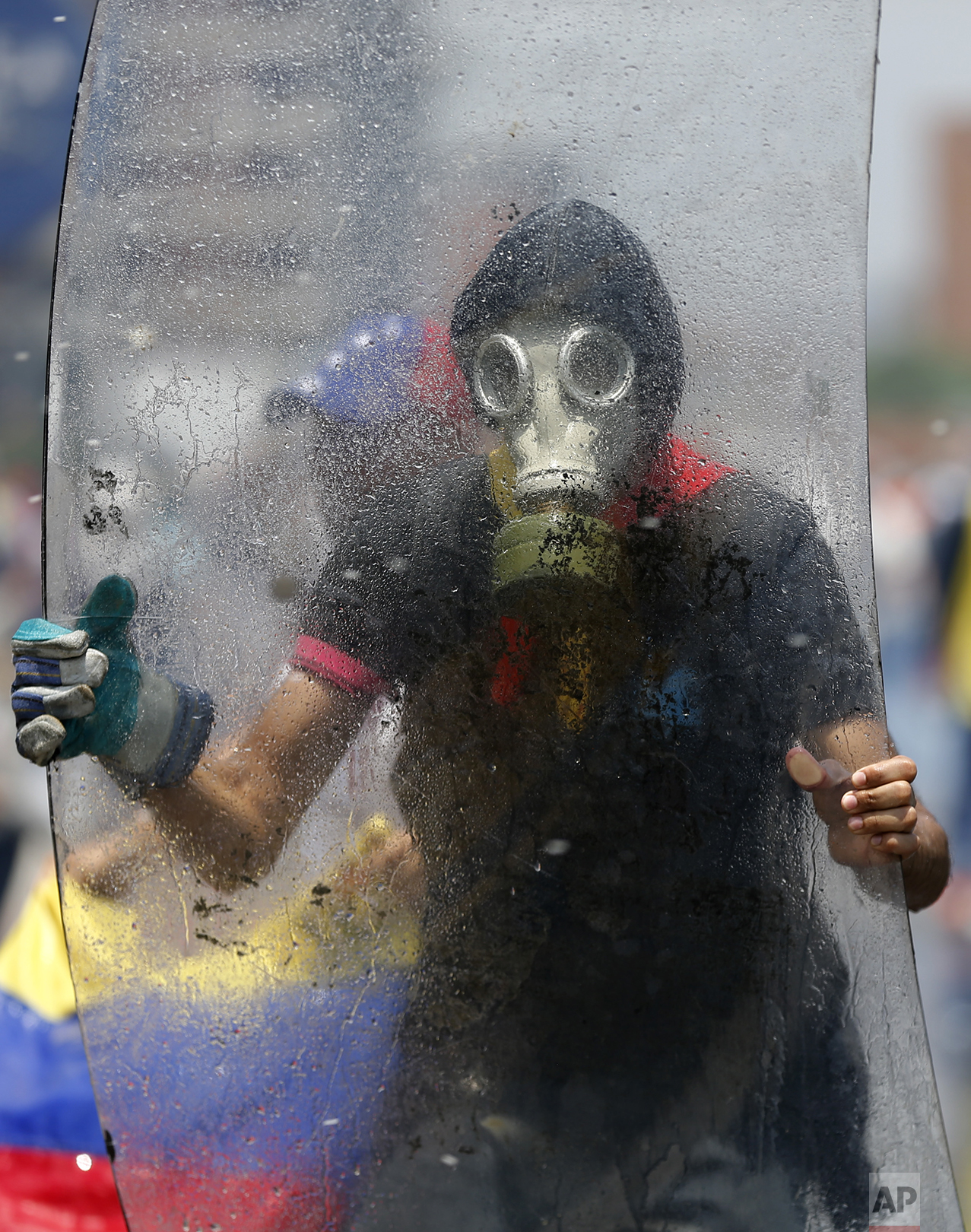 A protester holds an acrylic shield during clashes with security forces blocking opponents of President Nicolas Maduro in Caracas, Venezuela, Wednesday, April 26, 2017. Venezuela is threatening to pull out of the Organization of American States as the government's response to political unrest blamed for 27 deaths in recent weeks draws rebuke from the hemisphere's major powers. (AP Photo/Ariana Cubillos)