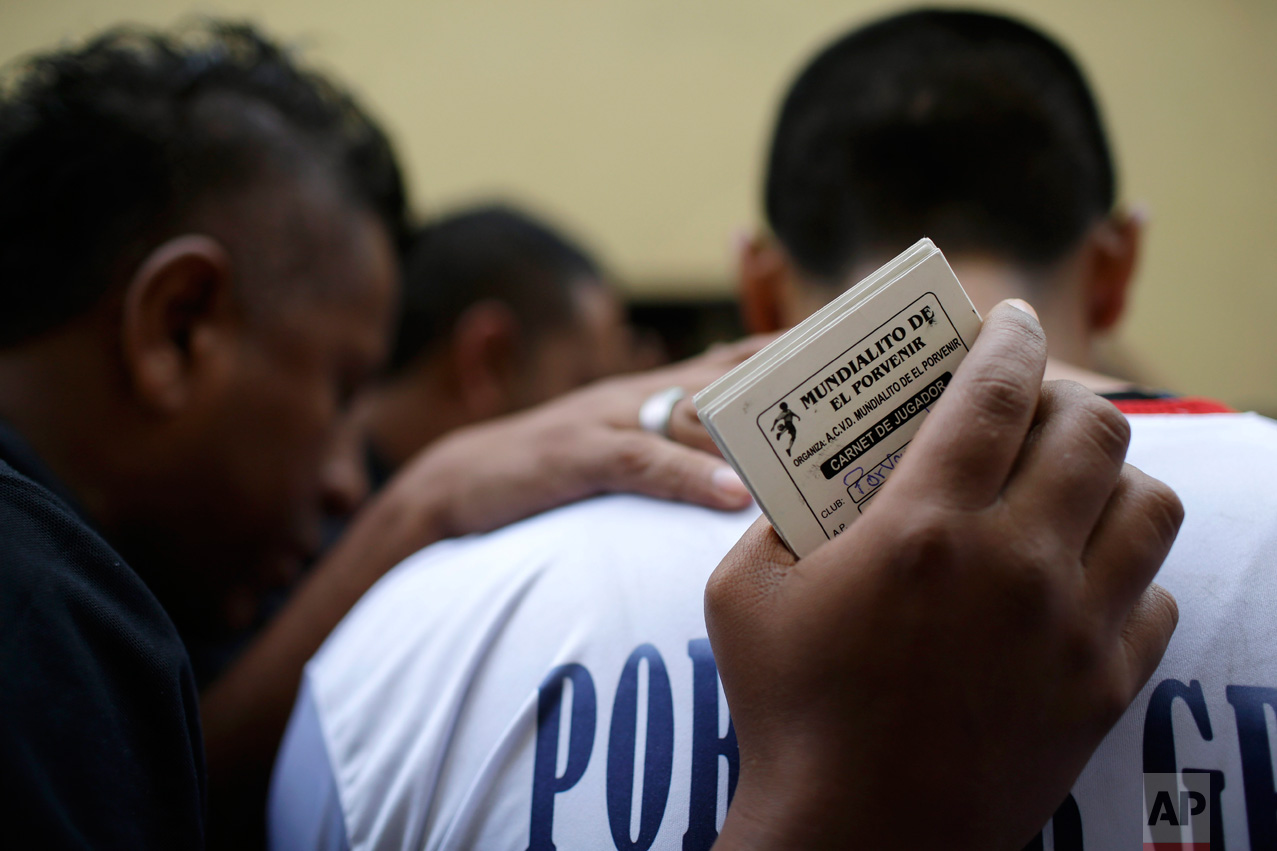"In this Monday, May 1, 2017 photo, the soccer team ""Porvenir Unidad"" prays before their game at the Little World Cup Porvenir street soccer championship in the Porvenir neighborhood of Lima, Peru. The annual May ritual saw 30 games played in the area's streets. (AP Photo/Martin Mejia)"