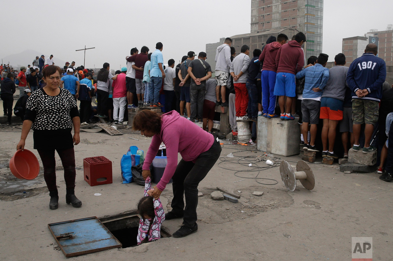 In this Monday, May 1, 2017, a woman helps a little girl down from a rooftop where fans watch the Little World Cup of Provenir street soccer championship in Lima, Peru. Spectators pay $2 dollars for a balcony view in apartment buildings to catch the games also known as The People's Party. (AP Photo/Martin Mejia)