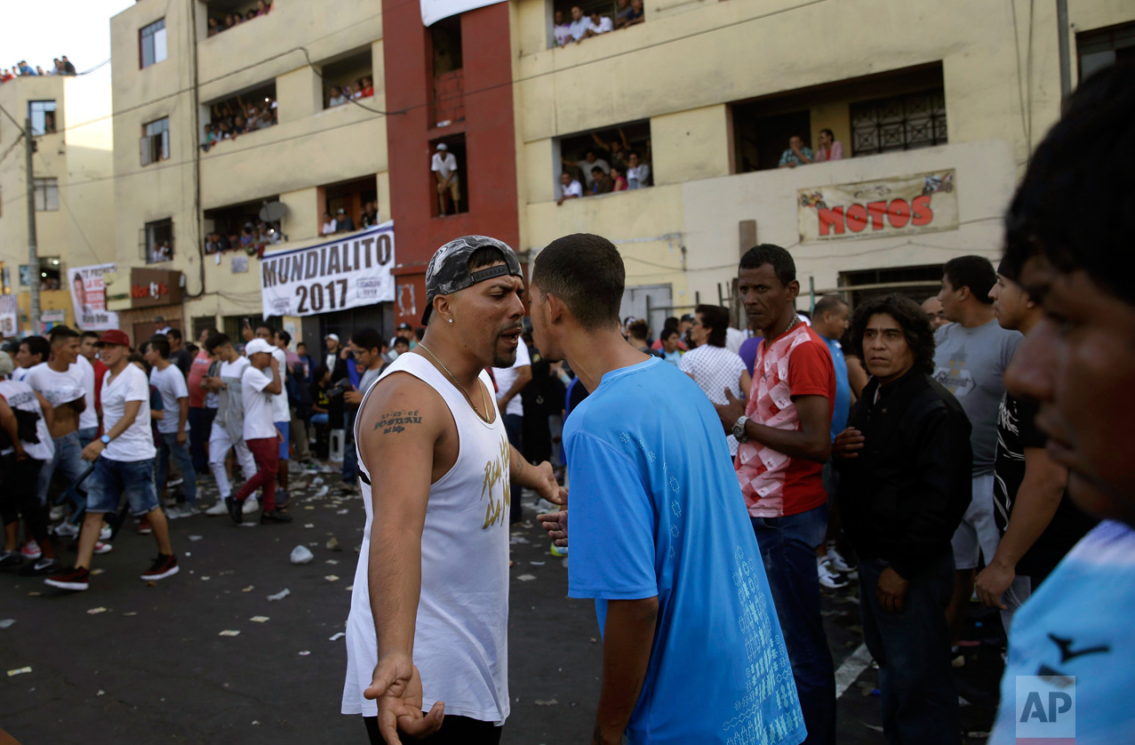 In this Monday, May 1, 2017 photo, fans of rival soccer teams argue at the end of the final game of Little World Cup of Provenir street soccer championship in Lima, Peru. The working-class neighborhood ritual in El Porvenir began in the 1950s as a challenge to the Manuel Odria military dictatorship when playing in the streets was forbidden. (AP Photo/Martin Mejia)