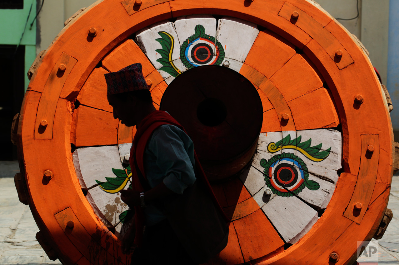 In this April 17, 2017 photo, a Hindu priest performs rituals in front of a wheel that will be part of the Rato Machindranath Chariot in Lalitpur, Nepal. The legend says that around the 7th century there was massive drought in the Kathmandu valley. It was believed that the arrival of the red deity would end the drought and bring back the rainfall. Hence then King Narendra Dev along with a priest and farmer travelled to what is now the Assam state in India and brought back Karunamaya, the god of compassion. It is popularly now known as Rato Machindranath. (AP Photo/Niranjan Shrestha)