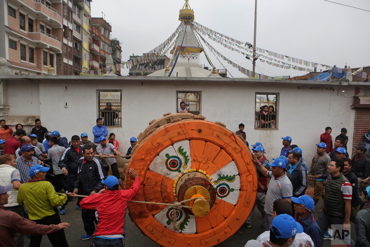 In this April 21, 2017, photo, locals and members of the Barahi community roll out a wheel to the construction site of the Rato Machindranath Chariot in Lalitpur, Nepal. The Barahis are responsible for repairing the giant wheels, carving the base and erecting the tower of logs for the chariot. The wooden chariot is built to appease the gods in hopes of being blessed with a good rainfall followed by a bountiful harvest. (AP Photo/Niranjan Shrestha)