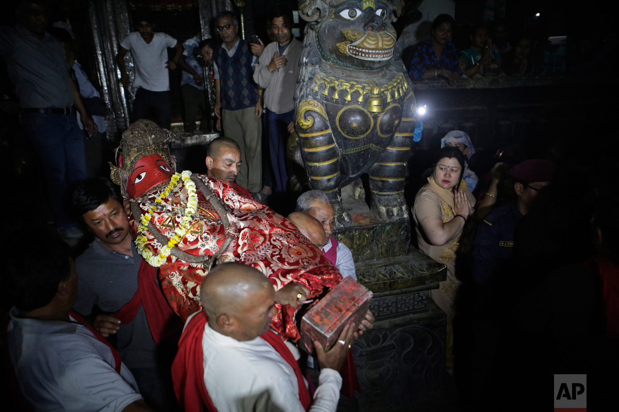 In this April 27, 2017, photo, Hindu priests carry the Rato machindranath deity to its seat inside a 15-meter (48-foot) tall wooden chariot to be taken around Patan city during an annual festival in Lalitpur, Nepal. Legend says that around the 7th century there was massive drought in the Kathmandu valley. It was believed that the arrival of the red deity would end the drought and bring back the rainfall. Hence then King Narendra Dev along with a priest and farmer travelled to what is now the Assam state in India and brought back Karunamaya, the god of compassion. It is popularly now known as Rato Machindranath. (AP Photo/Niranjan Shrestha)