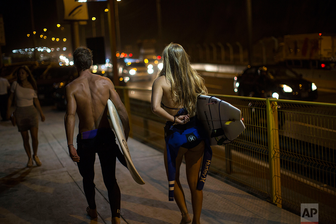In this Feb. 17, 2017 photo, surfers walk to La Pampilla beach in Lima, Peru. Night surfing apparently came about in Lima because of a dispute with the capital municipality that in 2015 increased the width of a road that runs along the coast. The surfers protested the construction for months by camping on the asphalted beach area, but in the end the municipality prevailed, with support from the police. At the end of 2016, perhaps to win over the surfers, Lima's mayor set up beach lights that allows for night surfing. (AP Photo/Rodrigo Abd)