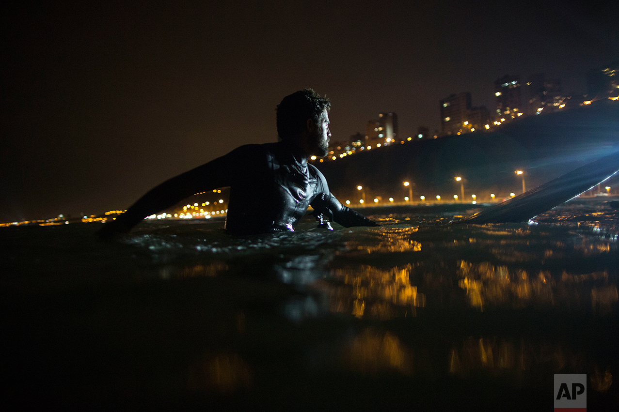 In this March 8, 2017 photo, Ernesto Benavides waits to catch a wave in La Pampilla beach in Lima, Peru. Night surfing came about in Lima because of a dispute with the capital municipality that in 2015 increased the width of a road that goes by the coast. (AP Photo/Rodrigo Abd)