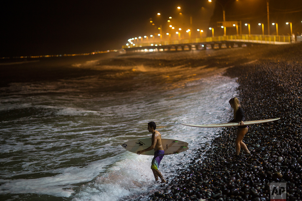 In this March 1, 2017 photo, surfers walk over the rocky shore into the Pacific Ocean at La Pampilla beach in Lima, Peru. The beach attracts fewer than two dozen surfers a night. (AP Photo/Rodrigo Abd)